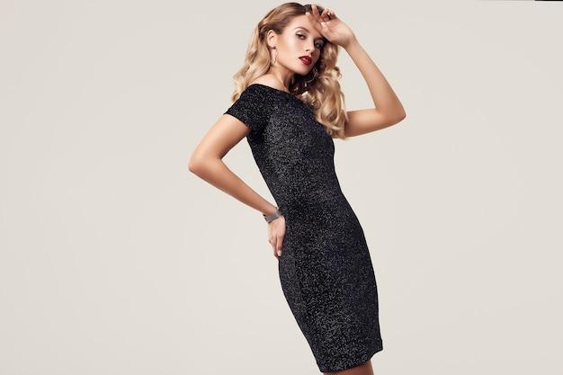 Portrait de magnifique femme blonde sensuelle élégante vêtue d'une robe noire fashion isolée sur un mur blanc