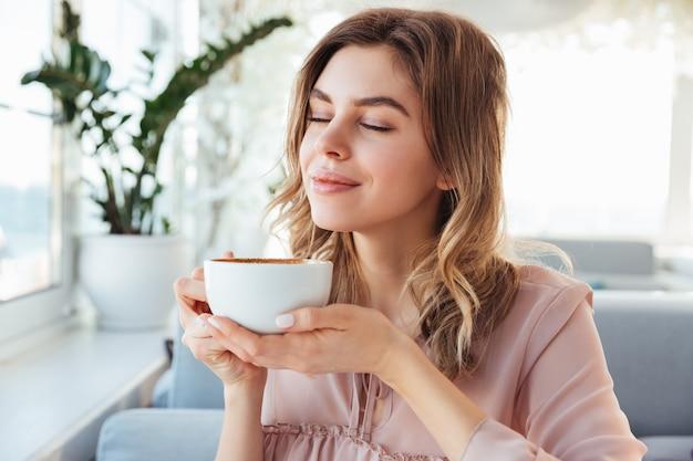 Portrait de magnifique femme souriante sentant et buvant du cappuccino de tasse, tout en se reposant au restaurant le matin