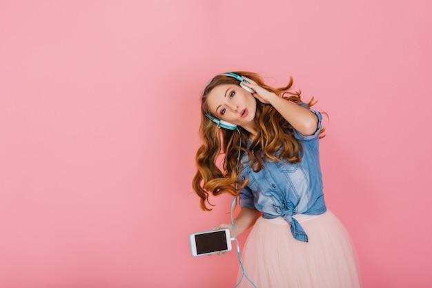 Portrait de magnifique fille aux cheveux longs heureuse dans les écouteurs chantant la chanson préférée isolée sur fond rose. jolie jeune femme bouclée en chemise en jean avec smartphone dansant et appréciant la musique