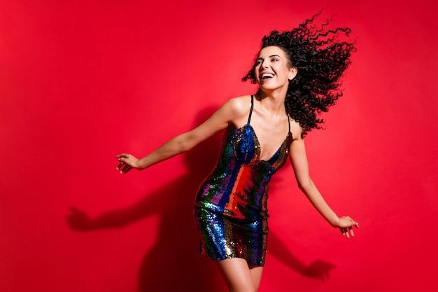 Portrait d'une magnifique fille aux cheveux ondulés gaie et gaie dansant s'amusant isolée sur fond de couleur rouge vif
