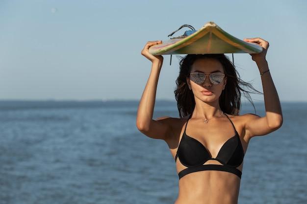 Portrait d'une magnifique fille brune dans un soutien-gorge noir et des lunettes de soleil tient une planche de surf au-dessus de sa tête près de la mer