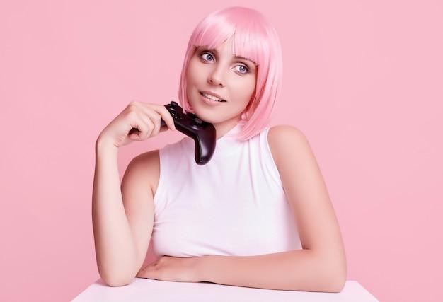 Portrait de magnifique fille heureuse gamer aux cheveux roses, jouer à des jeux vidéo à l'aide de joystick sur coloré en studio