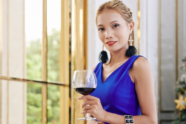 Portrait de magnifique jeune femme asiatique debout à la fenêtre avec un grand verre de vin rouge