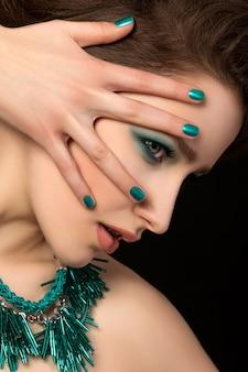 Portrait de la magnifique jeune femme aux ongles bleus et maquillage pour les yeux sur fond noir