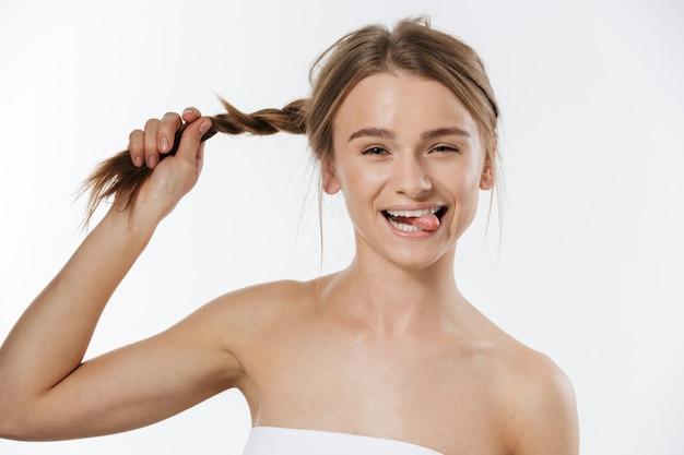 Portrait d'une magnifique jeune femme blonde à moitié nue souriante et tenant sa tresse isolée sur blanc