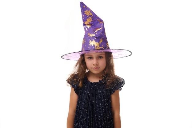 Portrait d'une magnifique petite fille confiante portant un chapeau de sorcier et vêtue d'une élégante robe de carnaval, regardant la caméra posant les bras croisés sur fond blanc, espace de copie.