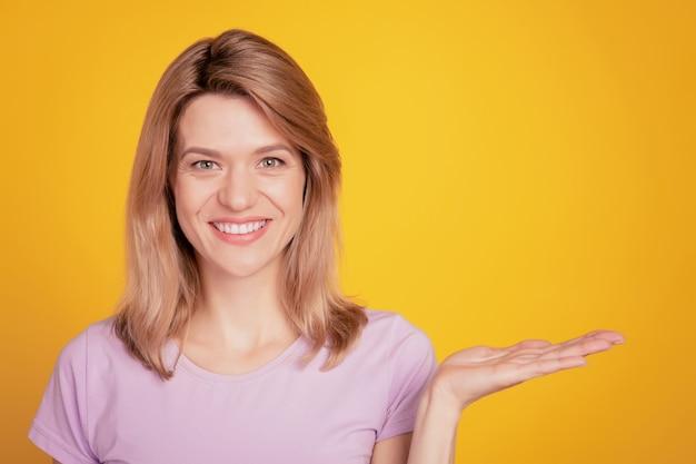 Portrait de la main de la conseillère positive show espace vide faisant la promotion de l'objet sur fond jaune