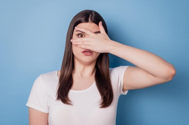 Portrait de main de dame stupéfaite sans voix fermer les yeux regardant la caméra sur fond bleu