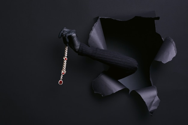 Portrait de la main de la femme en pull noir vole un collier de diamants dans un studio déchiré