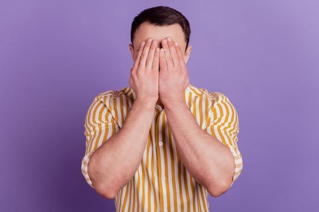 Portrait de mains désespérées de gars qui pleurent cacher le visage porter des vêtements décontractés sur fond violet