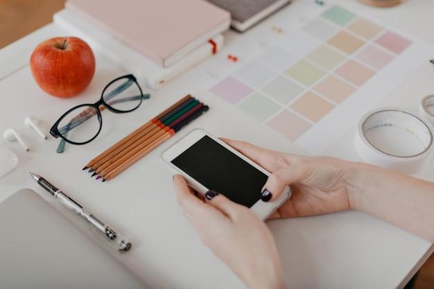 Portrait de mains féminines avec téléphone, pomme, lunettes, scotch et autres articles de papeterie sur blanc.