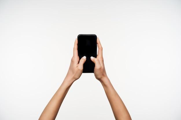 Portrait des mains levées de la jeune femme gardant le téléphone portable tout en tapant du texte avec les pouces, étant isolé sur blanc. concept de gestes et de signes de la main