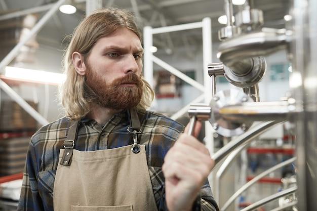 Portrait de maître brasseur barbu contemporain contrôlant la production à l'usine de fabrication de bière, espace de copie