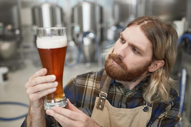 Portrait d'un maître brasseur barbu tenant un verre à bière tout en inspectant la qualité de la production à l'usine de brassage, espace de copie