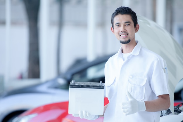 Portrait, mâle, mécanicien, porter, batterie voiture, dans, atelier