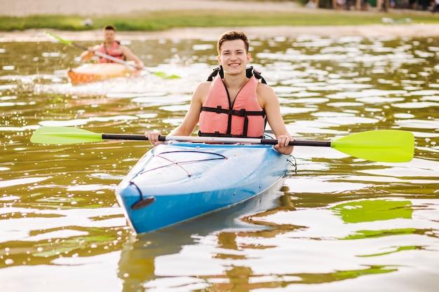 Portrait, de, mâle, tenue, pagaie, flottant, sur, kayak, sur, les, lac brillant