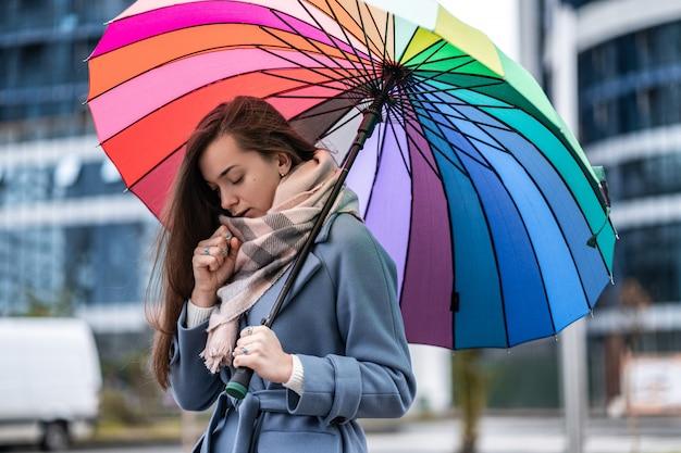 Portrait d'une malheureuse femme malade triste dans des vêtements chauds avec parapluie pendant le temps pluvieux froid à l'automne. saison du rhume et de la grippe. protection contre la pluie