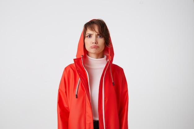 Portrait de malheureuse jeune belle heureuse dame aux cheveux courts en manteau de pluie rouge, regarde tristement avec les lèvres vers le bas. quelque chose ne va pas. des stands.