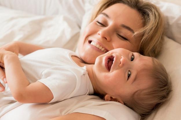Portrait de maman et bébé assis dans son lit