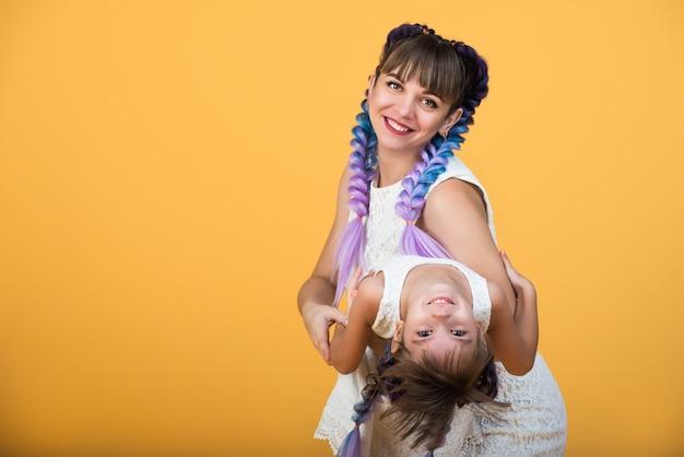 Portrait d'une maman joyeuse et fille positive avec les mêmes coiffures et robes posant en studio sur un mur jaune