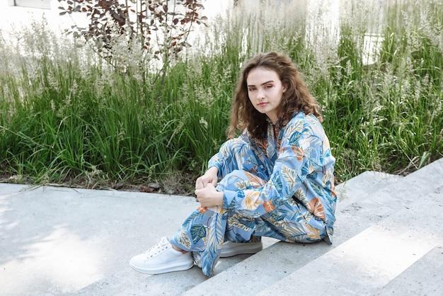 Portrait d'un mannequin assis sur les marches de la ville posant dans une nouvelle collection de vêtements