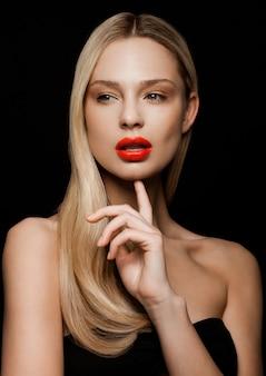 Portrait de mannequin de beauté avec une coiffure blonde brillante avec des lèvres rouges sur fond noir tenant le doigt à côté de son menton