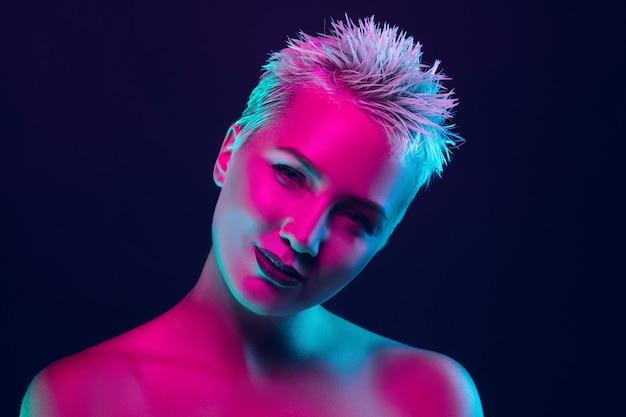 Portrait de mannequin femme en néon sur fond de studio sombre.