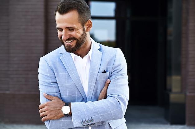 Portrait de mannequin homme d'affaires sexy beau vêtu d'un élégant costume bleu posant sur fond de rue. métrosexuel