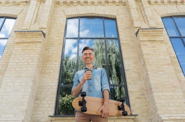 Portrait de mannequin mature élégant portant des vêtements décontractés, posant pour des photos à l'extérieur. patineur heureux tenant longboard, boire du café, marcher dans la rue, regardant la caméra et souriant