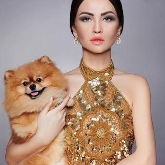 Portrait d'un mannequin avec un petit chien dans ses mains