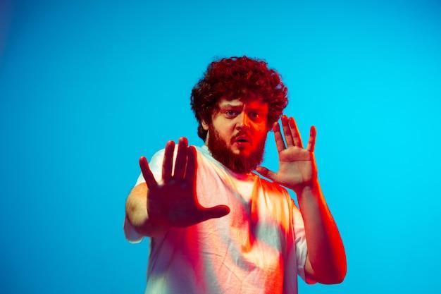 Portrait de mans caucasien isolé sur fond bleu studio en néon