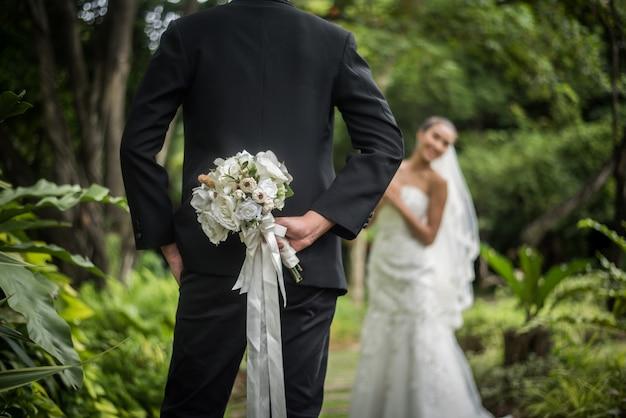 Portrait d'un marié cachant un bouquet de fleurs derrière son dos pour surprendre une mariée.