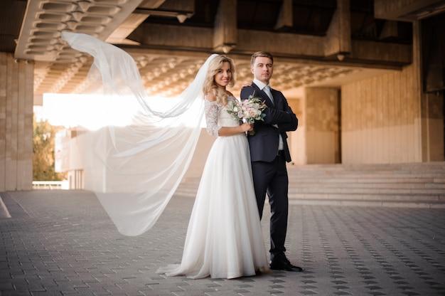 Portrait d'un marié debout avec une mariée blonde près du palais de mariage