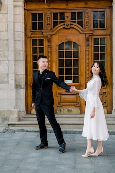 Portrait de marié et mariée chinois près de l'ancien bâtiment, vieille maison à l'extérieur, en plein air.