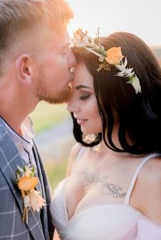 Portrait de marié qui embrasse la mariée tatouée avec décolleté ouvert et tendre couronne faite de fleurs fraîches