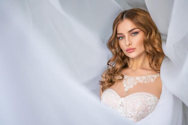 Portrait de la mariée, beau maquillage, voile de tissu blanc