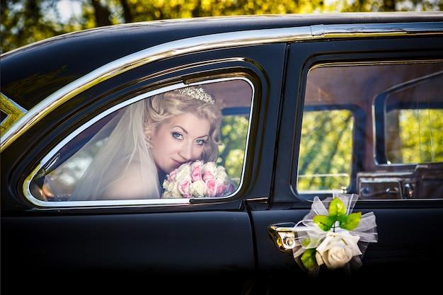 Portrait de la mariée dans une fenêtre d'un mariage rétro de la voiture