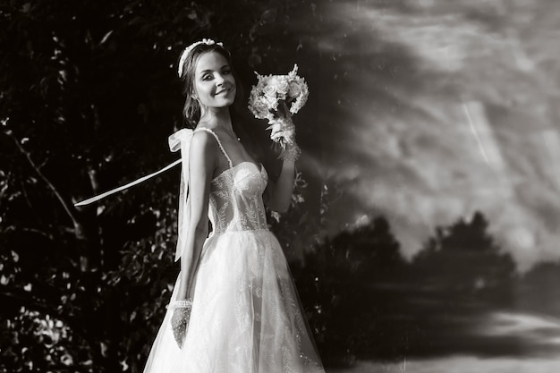 Portrait d'une mariée élégante dans une robe blanche avec un bouquet dans la nature dans un parc naturel.modèle dans une robe de mariée et des gants et avec un bouquet .biélorussie