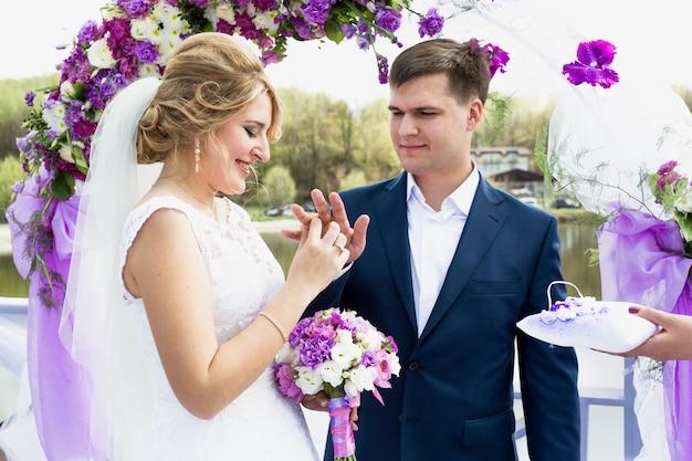 Portrait de mariée heureuse mettant l'anneau d'or sur la main du marié lors de la cérémonie de mariage