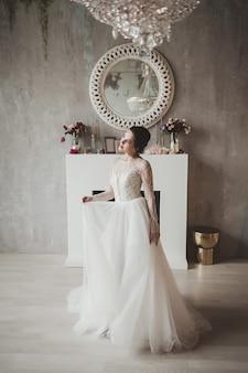 Portrait de mariée vêtue d'une robe de mariée de mode avec des plumes avec un maquillage et une coiffure de luxe