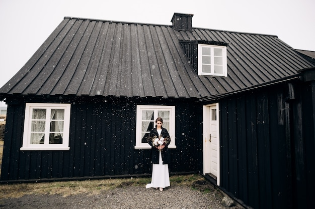 Portrait d'une mariée vêtue d'une robe de mariée en soie blanche et d'un manteau noir avec un bouquet de mariée en elle