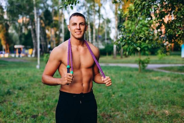 Portrait masculin, debout, corde à sauter, sur, pelouse, extérieur