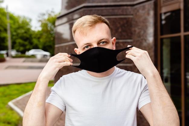 Portrait masculin. un homme au masque noir. quarantaine dans la ville.