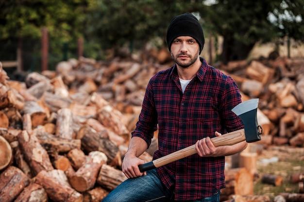 Portrait de la masculinité. jeune forestier confiant tenant une hache et regardant la caméra en se tenant debout à l'extérieur