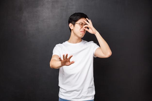 Portrait d'un mec asiatique réticent dégoûté, fermez le nez et détournez-vous de la mauvaise odeur désagréable, reniflez quelque chose de pourri, puant dégoûtant de la nourriture, levez la main en arrêt et le geste de refus,