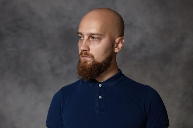 Portrait de mec barbu grincheux malheureux posant isolé. bouleversé maussade jeune homme de race blanche avec chaume et tête chauve havign pensif profondément dans l'expression du visage de pensées. les émotions humaines