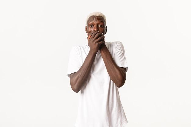 Portrait de mec blond afro-américain étonné et choqué, haletant avec la bouche couverte, à la surprise
