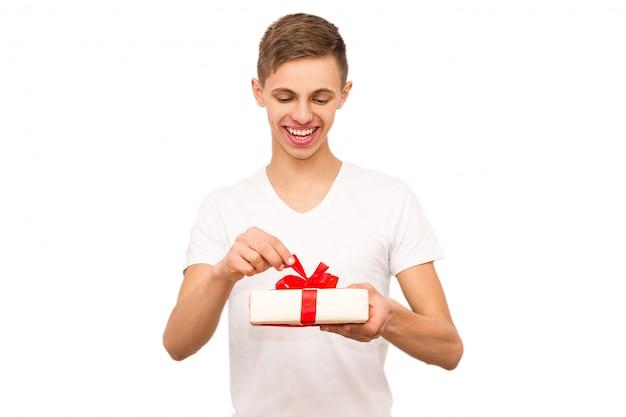 Portrait d'un mec avec un cadeau, isoler, le mec vêtu d'un t-shirt blanc fait un cadeau
