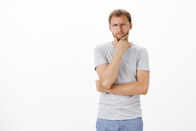 Portrait d'un mec caucasien douteux plissant les yeux en se frottant le menton et en regardant concentré tout en prenant une décision en hésitant et en se sentant douteux de la gestion de la pensée d'entreprise