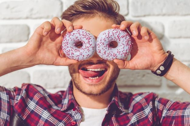 Portrait de mec drôle qui tient des beignets sur les yeux.
